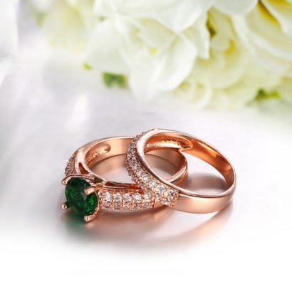 Copper twins ring inlaid with white crystals and a green olive special zircon