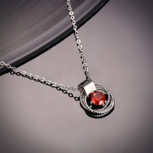 Braid necklace plated with platinum and has a red zircon in the middle