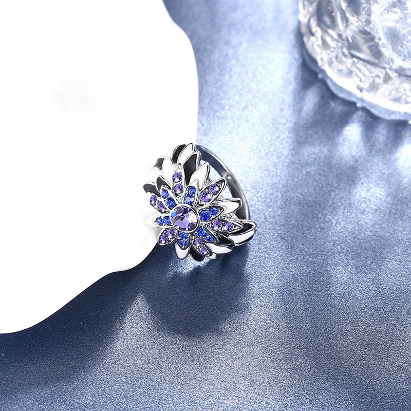 Water drop is a unique ring plated with platinum and inlaid withblue and violet diamond crystals and decorated by black oil drip