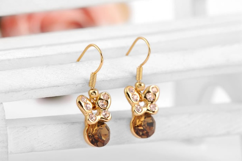 The butterfly earring is three times gold plated inlaid with genuine austrian white crystals and a champagne zircon