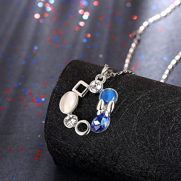A unique design of combined ornaments plated with platinum, inlaid with white opal, blue glass stone and a crystal diamond